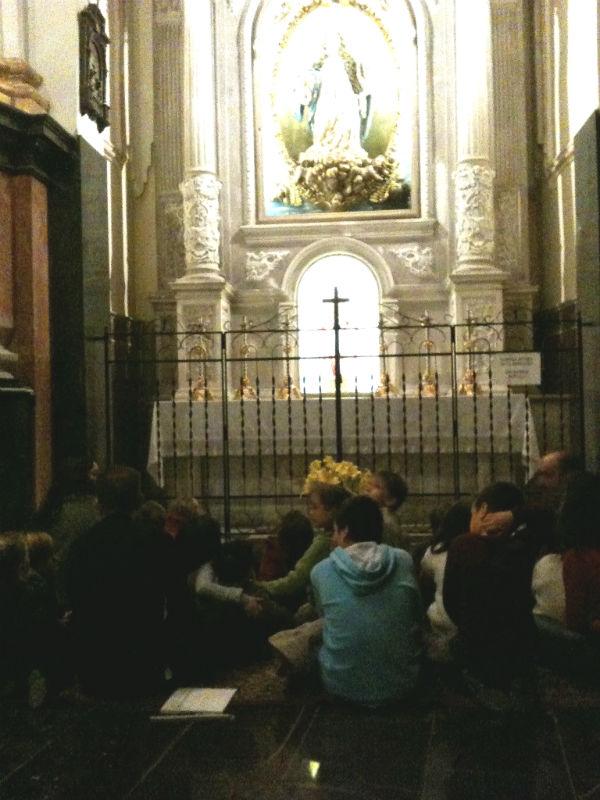 Los niños rezan frente a la Virgen de la Esperanza.